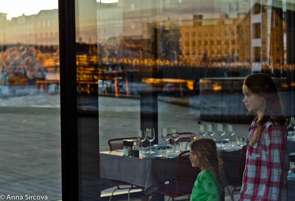 kids look out at the sunset from the Copenhagen Royal Theater restaurant with the cityscape reflecting in the big glass of the restaurant