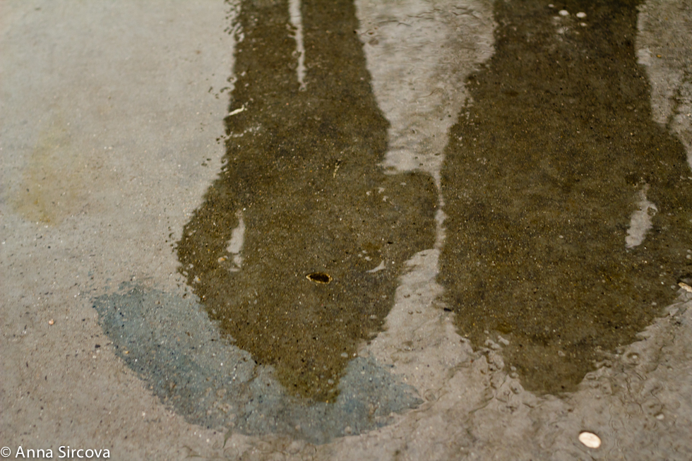 shadows of two people, one holding the umbrella, reflecting on wet pavement