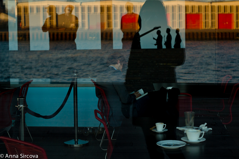 reflecting in the windows of the Copenhagen Royal Theater, someone drinking coffee, not paying attention to the beautiful sunset, photographs in the restaurant give an interesting interplay with forms and colors