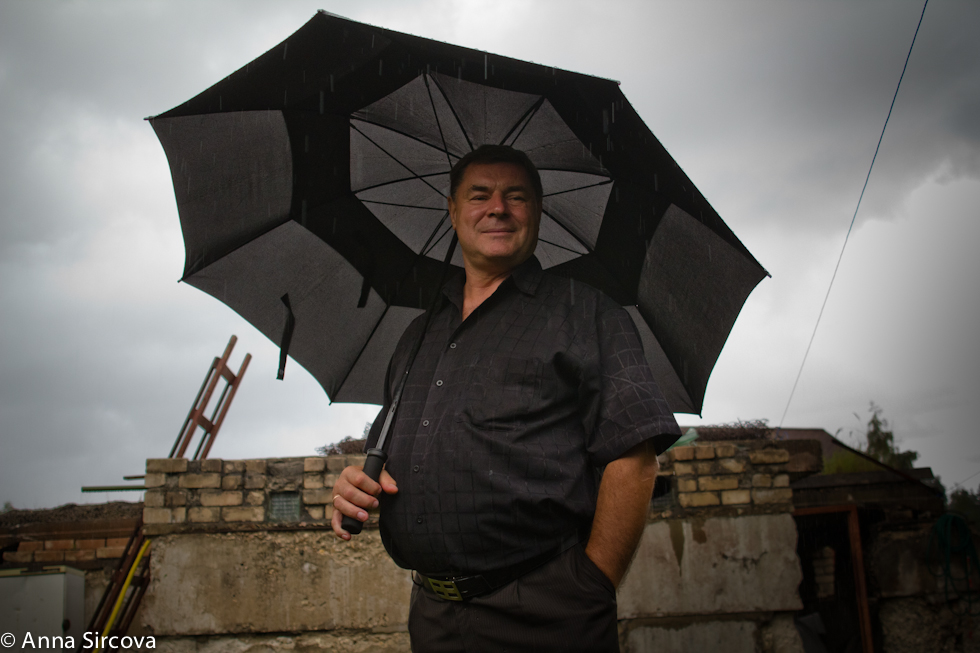 man holding a big black umbrella